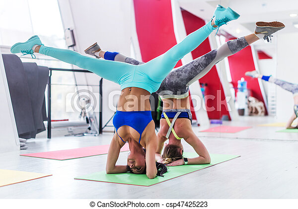 girls working out together doing wide leg headstand