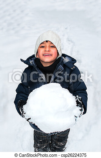 Junges, glückliches Kind, das im Schnee spielt - csp26224375