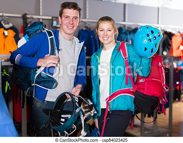 Glad adult couple is choosing travel gear - csp84023425