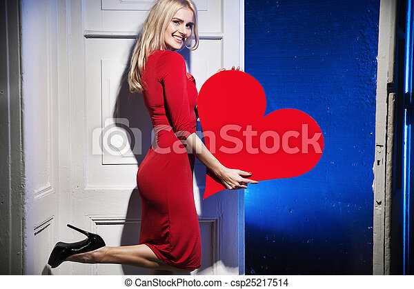 Glad and smiling woman holding a heart - csp25217514