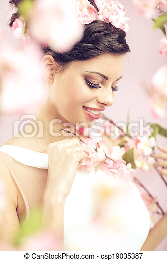 Glad brunette lady with the flowers in hair - csp19035387