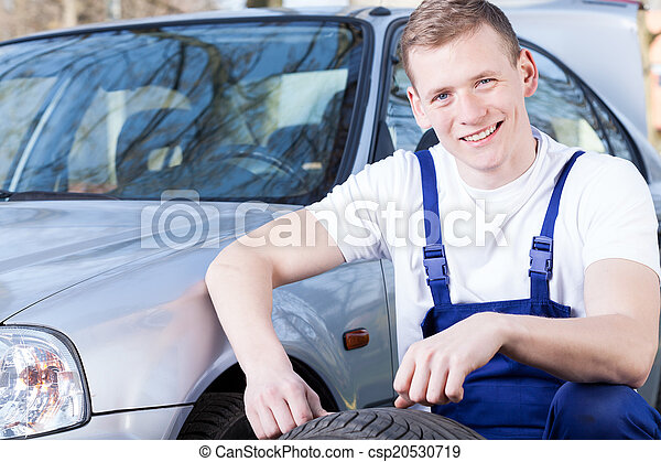 Glad mechanic changing a tire - csp20530719
