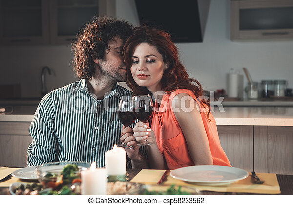 Glad young husband and wife clinking wineglasses in kitchen - csp58233562