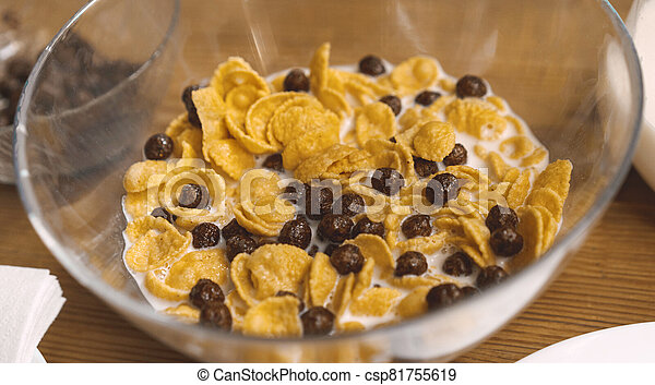 Glass bowl of Cornflakes with chocolate balls and milk on a wooden table. Cereal breakfast. Healthy quick food concept. Close up - csp81755619