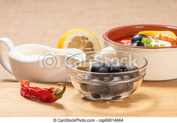 Glass bowl with black olives, dried red pepper on cutting board and ceramic soup bowl with saltwort, sauceboat and cut lemon. - csp69014664