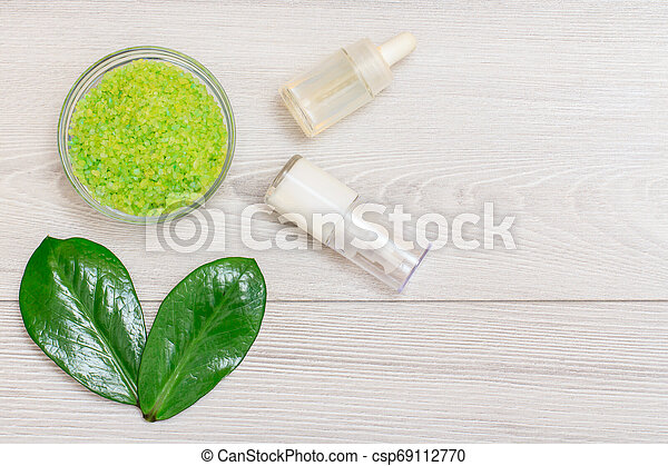 Glass bowl with sea salt, bottles with cream for face skin and aromatic oil and green leaves on gray background. - csp69112770