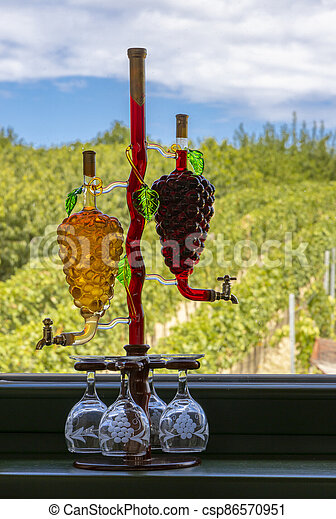 glass carafe with white and red wine in the shape of a grape and vineyard background - csp86570951