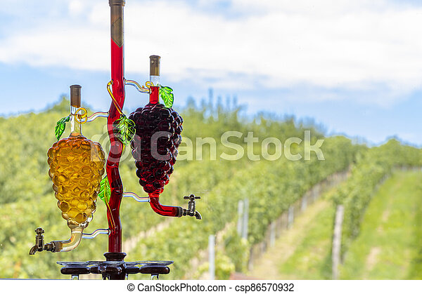glass carafe with white and red wine in the shape of a grape and vineyard background - csp86570932