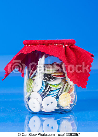 Glass Jar with Buttons Isolated on Blue. - csp13363057