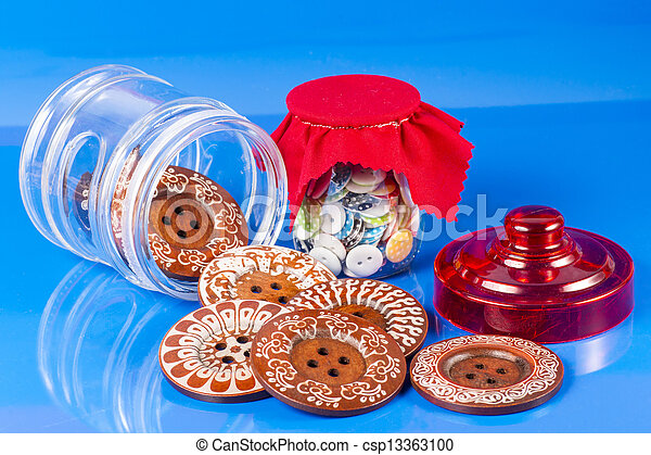Glass Jar with Buttons Isolated on Blue. - csp13363100