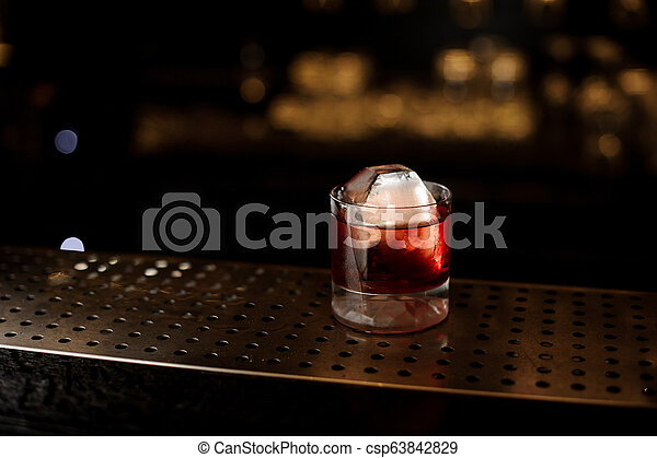 Glass of a Boulevardier cocktail on the steel wooden bar counter - csp63842829