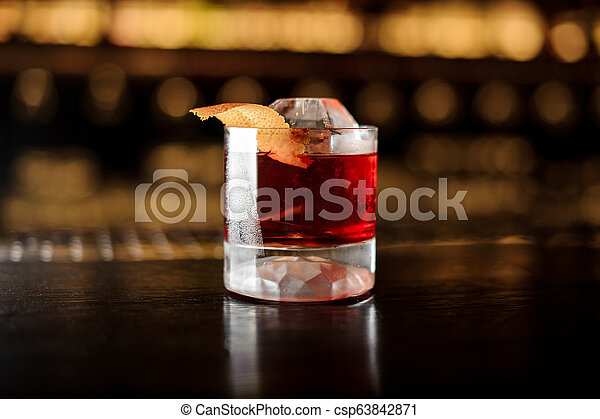 Glass of a Boulevardier cocktail with orange zest on the steel and wood bar counter - csp63842871
