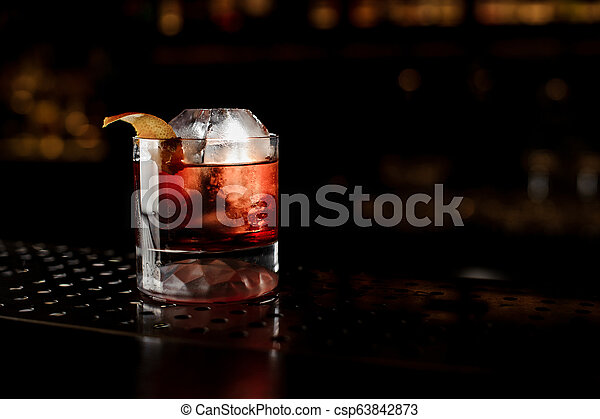 Glass of a Boulevardier cocktail with orange zest on the steel bar counter - csp63842873