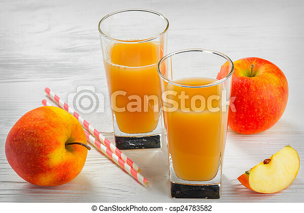Glass of apple juice with Apple slices on a white wood tray - csp24783582