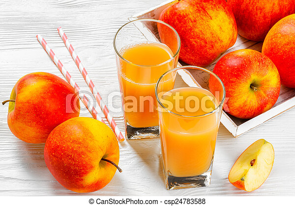 Glass of apple juice with apples on white wood background - csp24783588