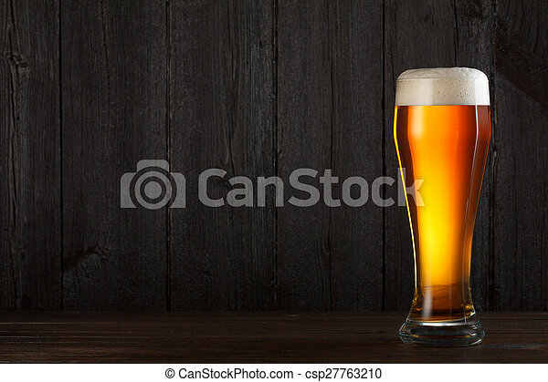 Glass of beer on wooden table - csp27763210