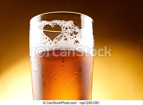 Glass of beer with the heart represented with froth close up over yellow background - csp12431261