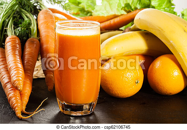 Glass of fruit juice with orange, carrots and banana - csp62106745