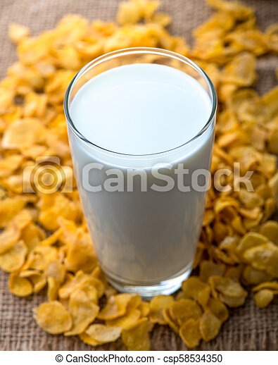 glass of milk and cereals on the wooden table - csp58534350
