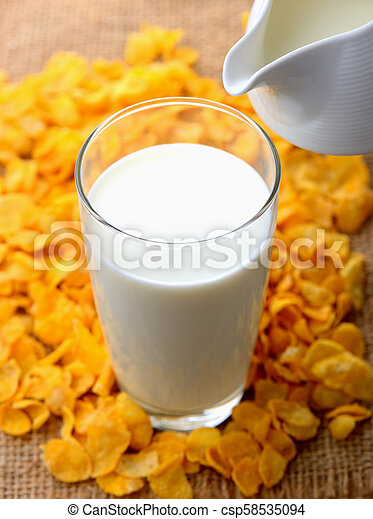 glass of milk and cereals on the wooden table - csp58535094