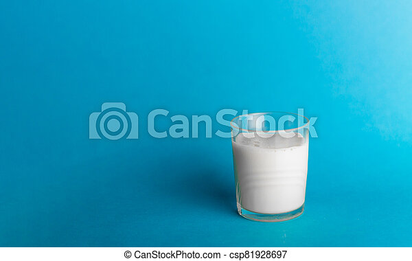 Glass of milk on blue background - csp81928697