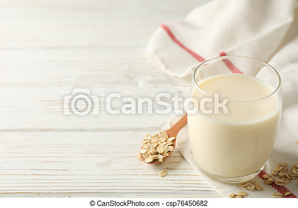 Glass of oat milk, spoon with oatmeal seeds and napkin on white, wooden background, space for text. Closeup - csp76450682