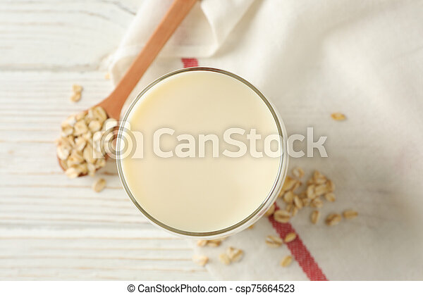 Glass of oat milk, spoon with oatmeal seeds and napkin on white, wooden background, top view. Closeup - csp75664523