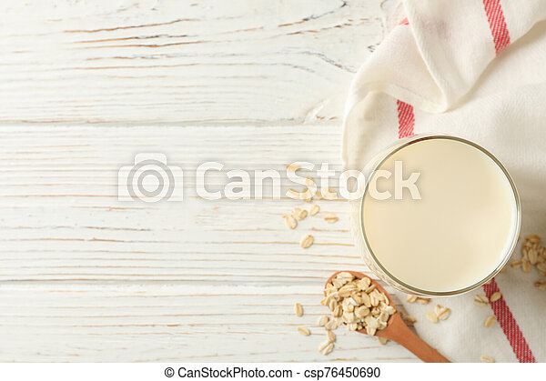 Glass of oat milk, spoon with oatmeal seeds and napkin on white, wooden background, top view. Space for text - csp76450690