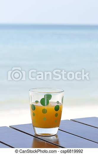 Glass of orange juice at the beach - csp6819992