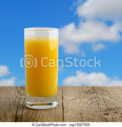 Glass of orange juice on wooden table on blue sky background - csp13027055