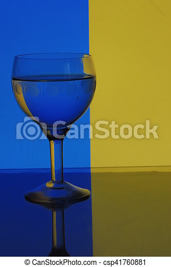 glass of water on blue yellow background - csp41760881
