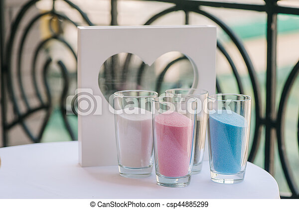 Glass vases with white, pink and blue sand and frame like heart staying on table