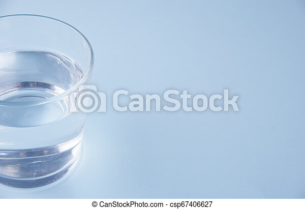 Glass with water on a blue background - csp67406627