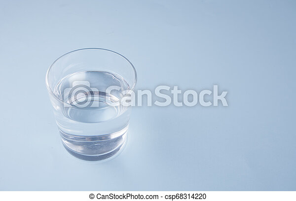 Glass with water on a blue background - csp68314220