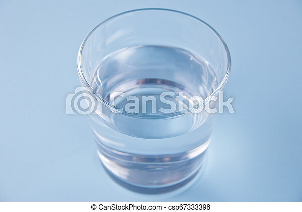 Glass with water on a blue background - csp67333398