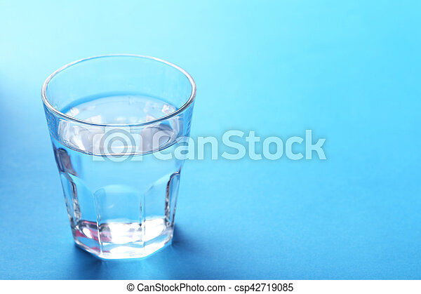 Glass with water on blue background - csp42719085