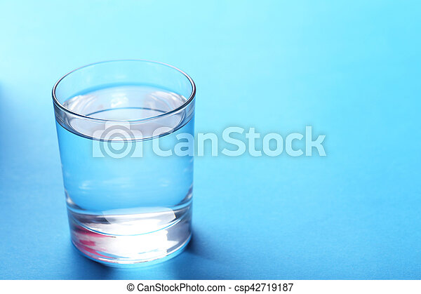 Glass with water on blue background - csp42719187