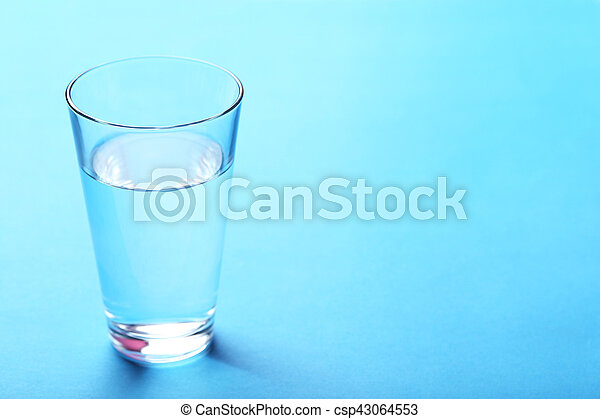 Glass with water on blue background - csp43064553