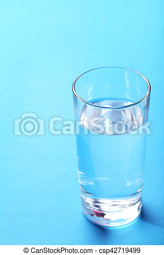 Glass with water on blue background - csp42719499