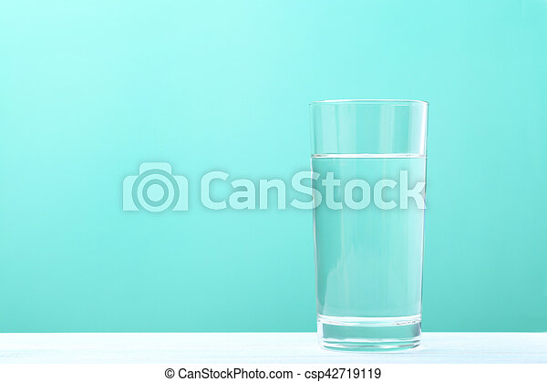 Glass with water on mint background - csp42719119