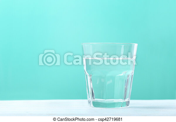 Glass with water on mint background - csp42719681