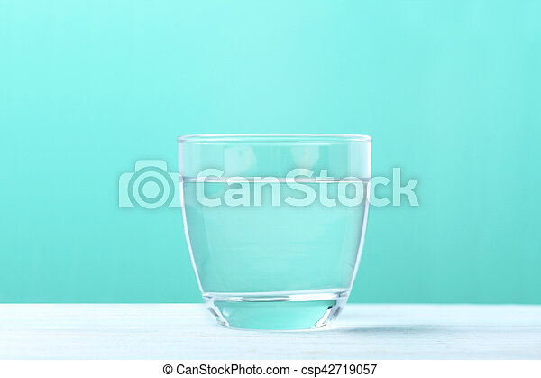 Glass with water on mint background - csp42719057