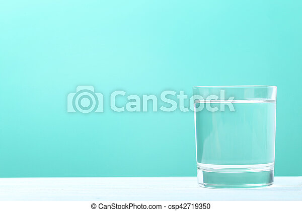 Glass with water on mint background - csp42719350