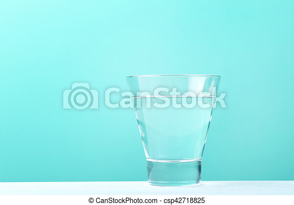 Glass with water on mint background - csp42718825