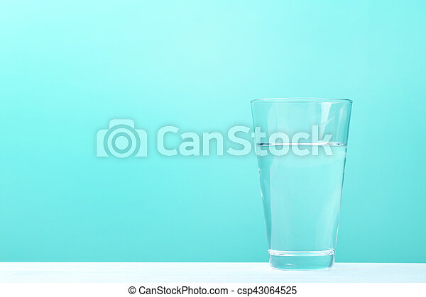 Glass with water on mint background - csp43064525