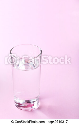 Glass with water on pink background - csp42719317