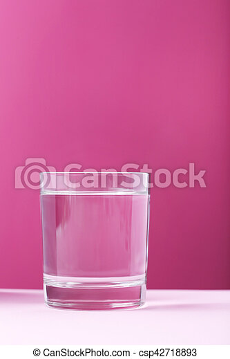 Glass with water on pink background - csp42718893
