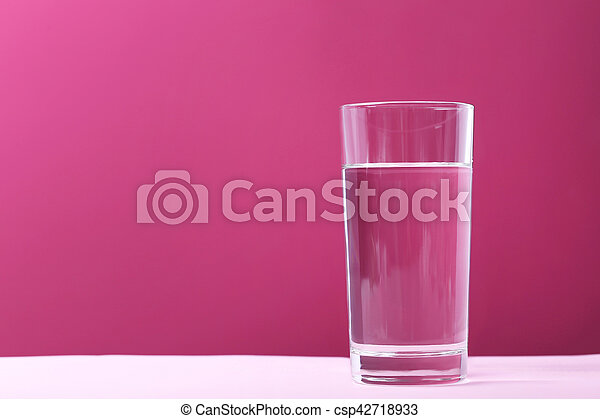 Glass with water on pink background - csp42718933