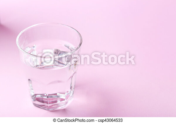 Glass with water on pink background - csp43064533