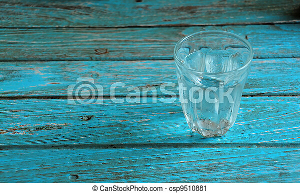 Glass with water on the cyan wood - csp9510881